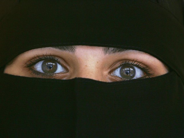 BLACKBURN, UNITED KINGDOM - OCTOBER 06: A Muslim woman wearing a Niqab poses inside an Asian fashion shop in the British northern town of Blackburn, the constituency of Member of Parliament Jack Straw, where a quarter of his constituents are Muslim on October 6, 2006, Blackburn, England. Leader of the …
