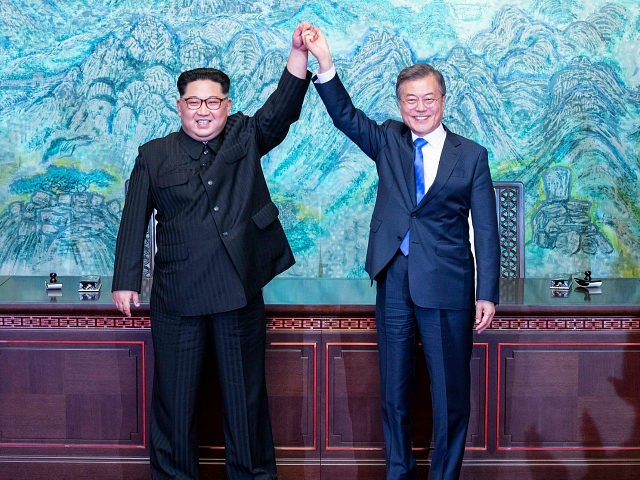 North Korean leader Kim Jong Un left and South Korean President Moon Jae-in raise their hands after signing on a joint statement at the border village of Panmunjom in the Demilitarized Zone South Korea Friday
