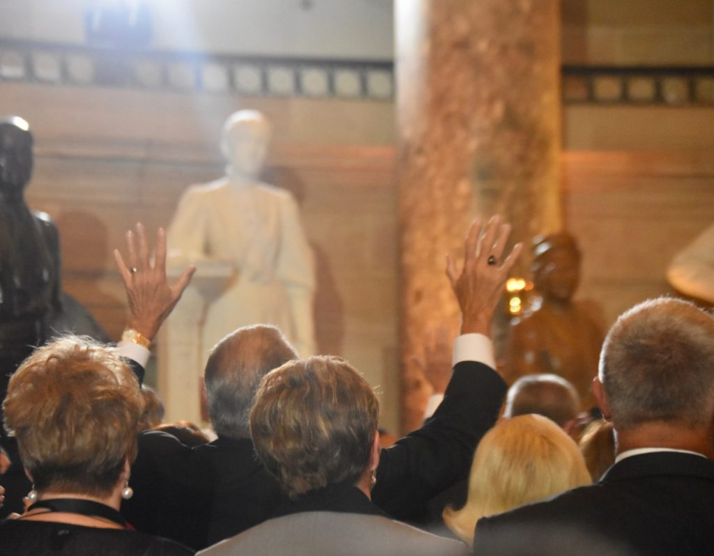People lifted their hands as Gospel music filled Statuary Hall in the nation's Capitol on Thursday to mark the National Day of Prayer. (Penny Starr/Breitbart News)