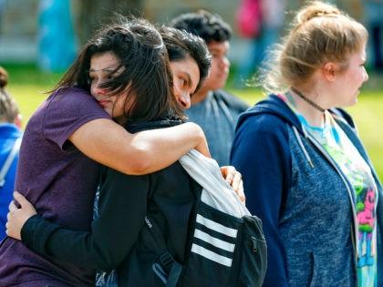 Santa Fe High School freshman Caitlyn Girouard, center, hugs her friend outside the Alamo Gym where students and parents wait to reunite following a shooting at Santa Fe High School Friday, May 18, 2018, in Santa Fe, Texas. (Michael Ciaglo/Houston Chronicle via AP)