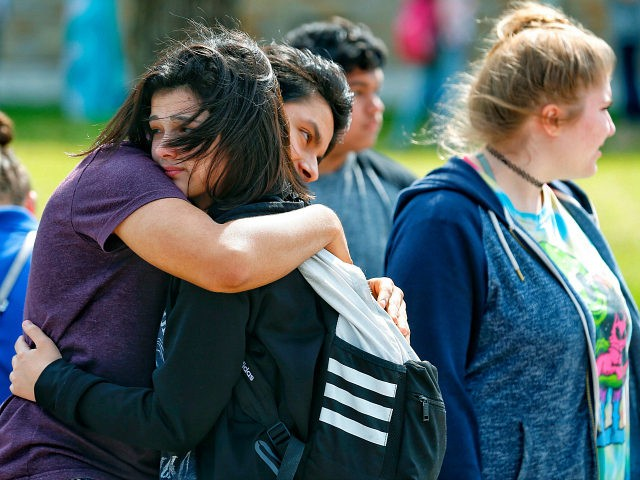 Santa Fe High School freshman Caitlyn Girouard, center, hugs her friend outside the Alamo Gym where students and parents wait to reunite following a shooting at Santa Fe High School Friday, May 18, 2018, in Santa Fe, Texas. (Michael Ciaglo/Houston Chronicle via AP)