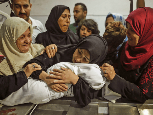 The mother of a Leila al-Ghandour (C), a Palestinian baby of 8 months who according to Gaza's health ministry died of tear gas inhalation during clashes in East Gaza the previous day, holds her at the morgue of al-Shifa hospital in Gaza City on May 15, 2018 - Fresh protests …