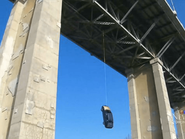 Toronto cops are left stumped by sight of blue sedan dangling by a rope from one of city's busiest bridges