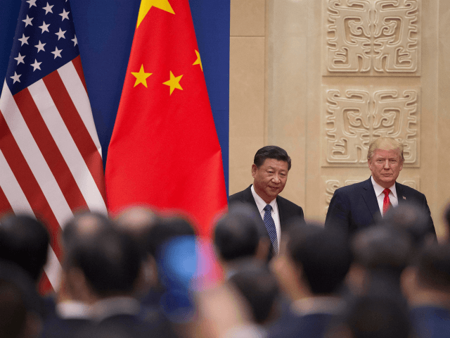 US President Donald Trump (R) and China's President Xi Jinping (L) arrive at a business leaders event inside the Great Hall of the People in Beijing on November 9, 2017. Donald Trump urged Chinese leader Xi Jinping to work 'hard' and act fast to help resolve the North Korean nuclear …