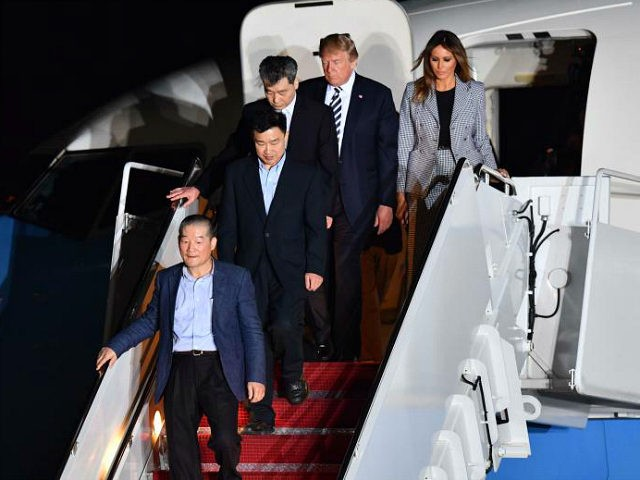 US President Donald Trump (2nd R) and his wife Melania Trump (R) walk down the stairs with US detainees Tony Kim (2nd L), Kim Dong-chul (bottom L) and Kim Hak-song (C) upon their return after they were freed by North Korea, at Joint Base Andrews in Maryland on May 10, …