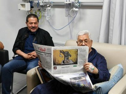 Palestinian Authority President Mahmoud Abbas shown recovering in hospital and reading a newspaper on the back page of which is a cartoon portraying an Israeli soldier poisoning a Palestinian baby, May 22, 2018. . (Wafa news agency)