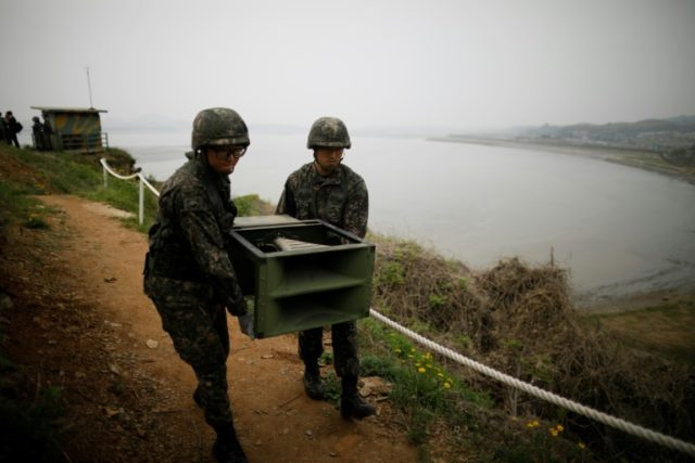 South Korean soldiers remove loudspeakers that were used to blare K-pop and news towards the North' troops