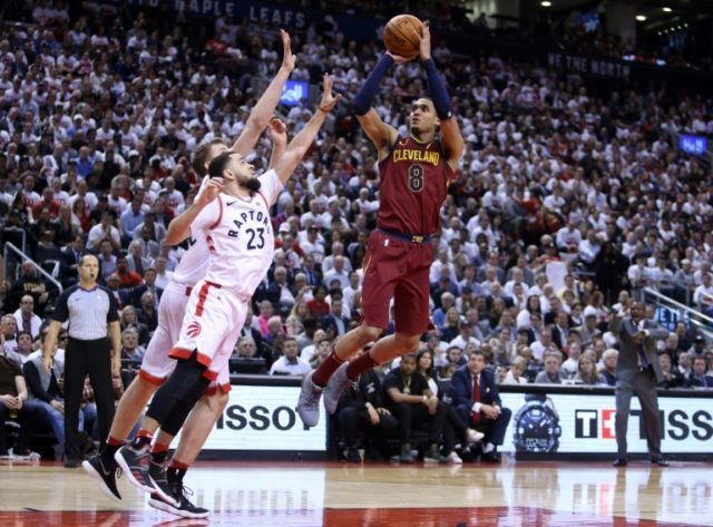 Jordan Clarkson of the Cleveland Cavaliers shoots over Jonas Valancianas and Fred VanVleet of the Toronto Raptors as Cleveland take game one of the second-round series