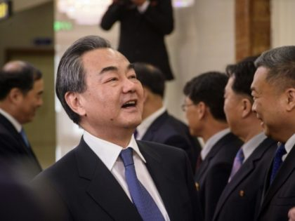 China's foreign minister Wang Yi (L) laughs as he shakes hands with North Korea's vice foreign minister Ri Kil Song at Pyongyang airport