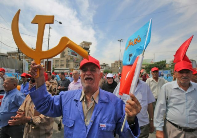 A supporter of Iraq's Communist Party holds the communist hammer and sickle and the flag of the Marching Towards Reform joint list during a May Day march in Baghdad on May 1, 2018
