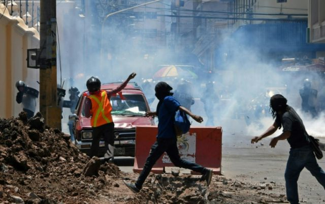Demonstrators clash with riot police during a May Day protest demanding the resignation of President Juan Orlando Hernandez in Tegucigalpa on May 1st, 2018