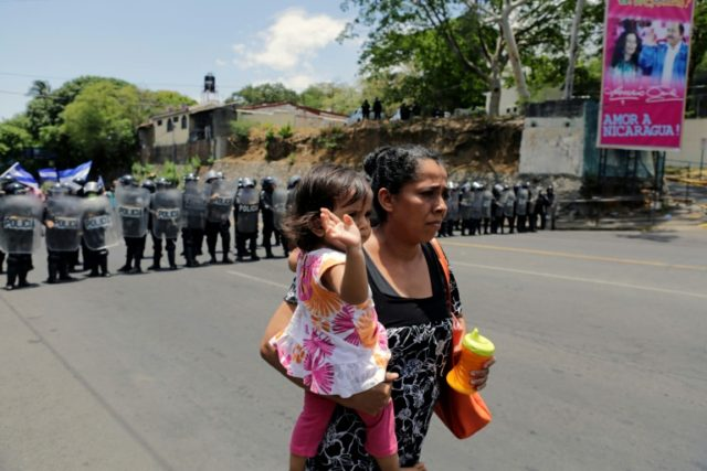 A woman carrying her baby walks in front of riot police blocking the road as demonstrators protest during a march to demand justice over 43 deaths in recent protests un en el marco de protestas A woman carrying her baby walks in front of riot police agents blocking the road …