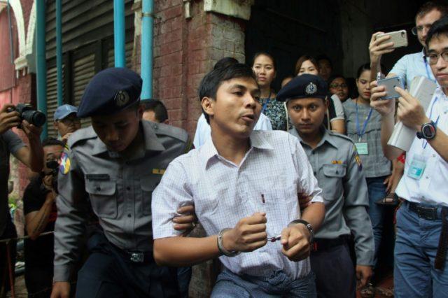 Detained Myanmar journalist Kyaw Soe Oo (C) is escorted by police to court