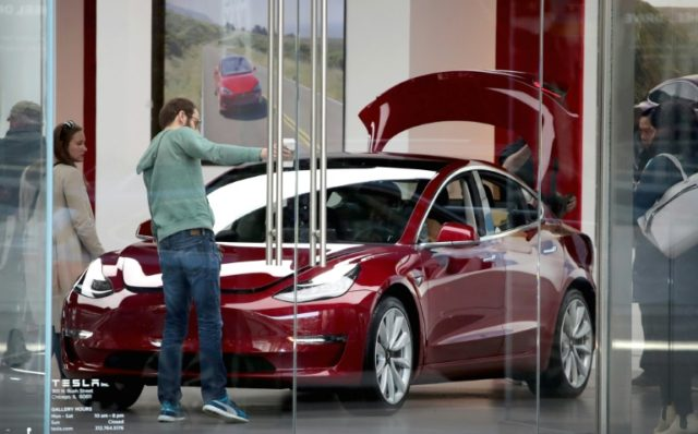 A Tesla Model 3 sits on the showroom floor at a dealership in Chicago, Illinois in March 2018; the car is considered key to Tesla's success in the mass market