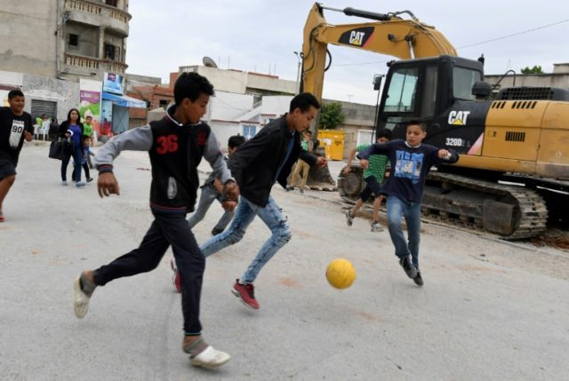 Children play football in the streets of Ettadhamen city on April 30, 2018, an impoverished area of Greater Tunis