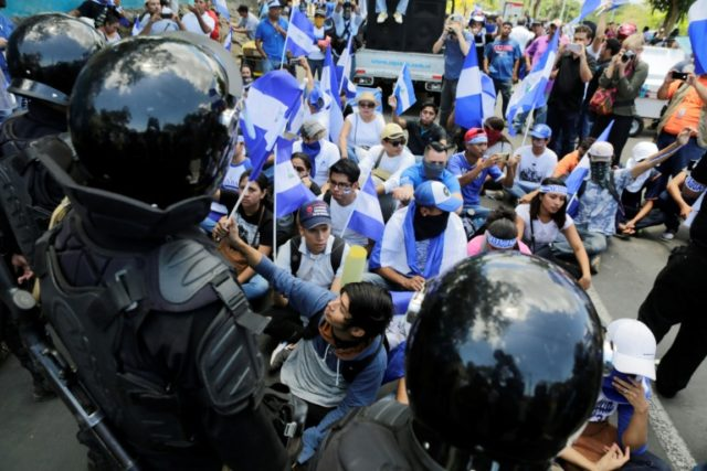 Nicaraguan demonstrators sit in front of riot police agents blocking their march to demand justice for 43 people killed in recent protests; the Central American country has been hit by protests demanding President Daniel Ortega's ouster since April 18