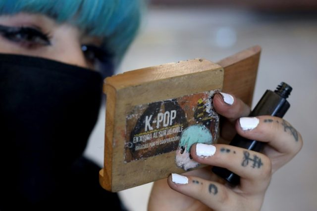 "A member of Chile's ""Rough Bunnies,"" a K-pop tribute band, puts on her makeup before performing in Santiago"