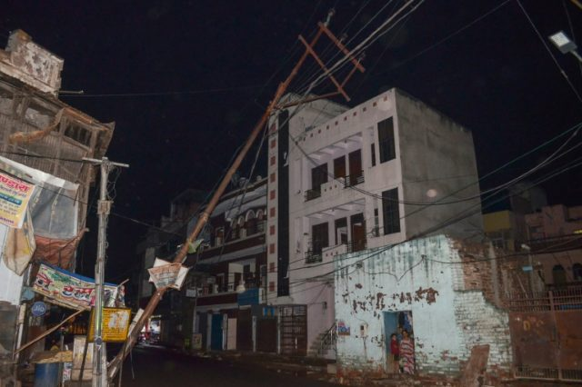 Residents (lower R) look out from their home next to a fallen electricity line following a major storm in Agra in northern India's Uttar Pradesh state on May 2, 2018