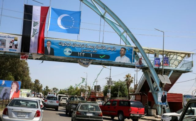 A picture taken on April 30, 2018, shows an electoral banner for the Iraqi Turkmen Front hanging beneath the flags of Iraq (L) and the Iraqi Turkmen (C) above a pedestrian crossing in the oil-rich and multi-ethnic northern city of Kirkuk
