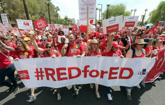 Thousands of Arizona teachers march through downtown Phoenix on their way to the State Capitol as part of a rally for on April 26, 2018 in Phoenix, Arizona