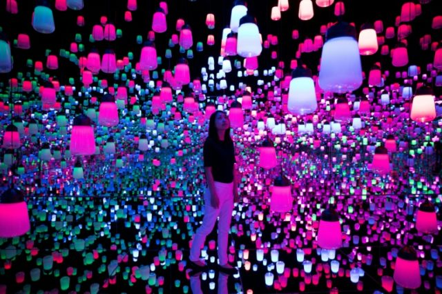 A member of the teamLab collective walks through a digital installation room in Tokyo featuring hanging lamps that light up as the visitor nears