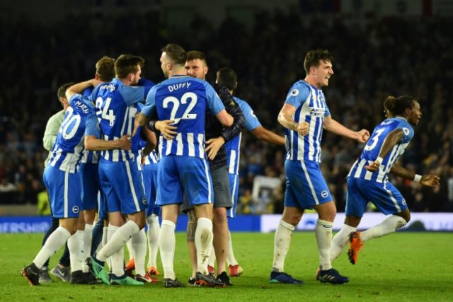 Brighton's players celebrate secured their place in the Premier League next season as Pacal Gross's solitary goal inflicted a 1-0 defeat on Manchester United on Friday