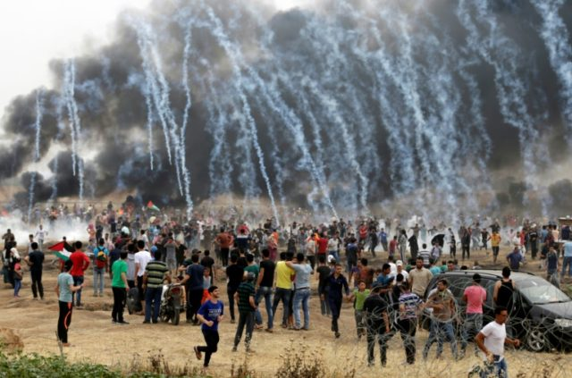 Palestinian protesters flee from incoming teargas canisters during clashes with Israeli forces along the border with the Gaza strip east of Gaza City on May 4, 2018, on the sixth straight Friday of mass demonstrations