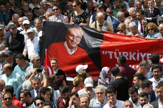 Turkey's main opposition Republican People's Party (CHP) supporters display a banner as they listen to their candidate for the upcoming snap presidential election Muharrem Ince during the start of his campaign in Ankara on May 4, 2018
