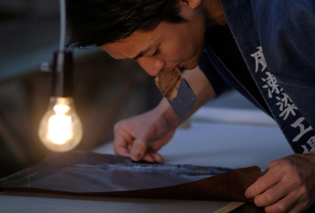 Yuichi Hirose holds a hand-cut stencil to dye a kimono at a century-old workshop in Tokyo