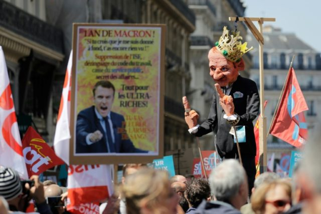 """A protester holds a figure mocking Emmanuel Macron at the """"The party for Macron"""" rally to protest the policies of the French president on the first anniversary of his election"""