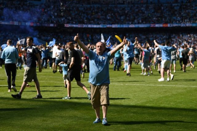 City fans invade the pitch after the 0-0 draw with Huddersfield at the Etihad Stadium on Sunday
