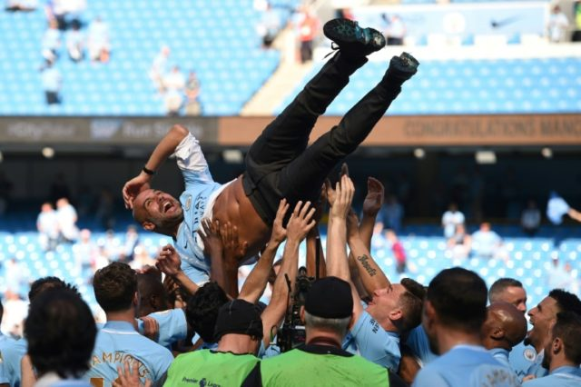 Manchester City players celebrating their title win with manager Pep Guardiola