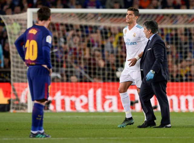 Real Madrid's forward Cristiano Ronaldo (L) walks with his team's doctor after an injury during a Spanish league football match against Barcelona