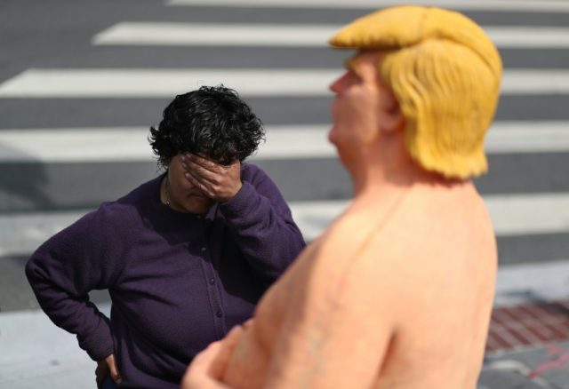 A passerby next to a statue depicting Donald Trump in the nude in San Francisco in August 2016