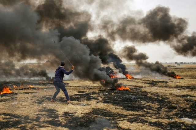 A Palestinian protester uses a sling to hurl stones towards Israeli forces during clashes along the border of the Gaza Strip on May 4, 2018