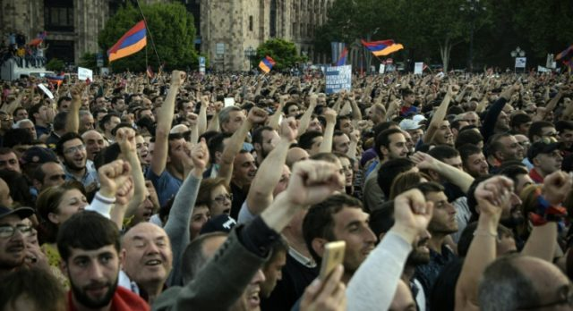 Protestors shout slogans and wave flags in Yerevan after the ruling party rejected Pashniyan's first attempt to be elected premier