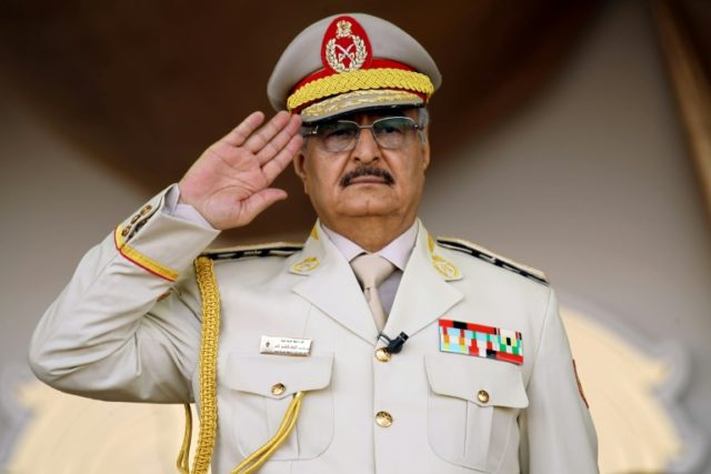 """Libyan strongman Khalifa Haftar salutes during a military parade in the eastern city of Bengahzi on May 7, 2018, during which he announced a military offensive to take from """"terrorists"""" the city of Derna"""