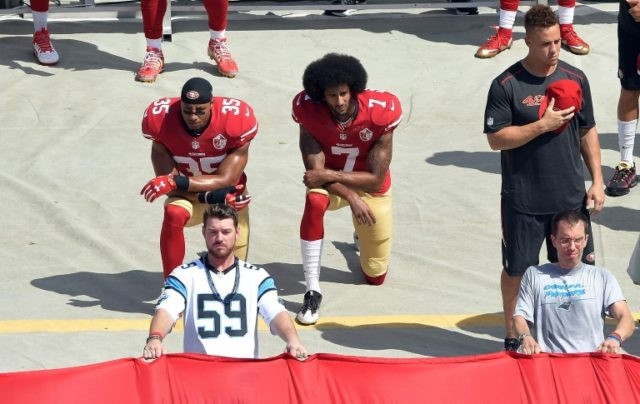 Colin Kaepernick (R) and Eric Reid of the San Francisco 49ers kneel during the national anthem before a NFL game in 2016