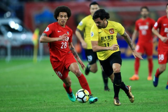 Guangzhou's Ricardo Goulart (R) fights for the ball with Tianjin's Axel Witsel during their AFC Champions League clash