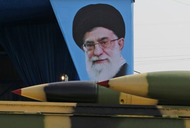 An Iranian military truck carries surface-to-air missiles past a portrait of supreme leader Ayatollah Ali Khamenei during a parade in Tehran on April 18, 2018