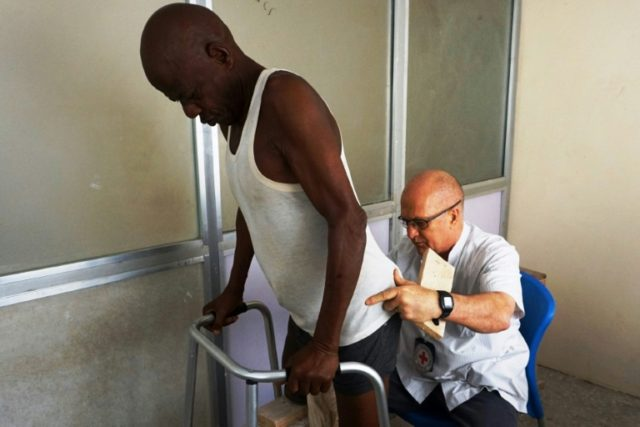Prosthetist Jacques Forget examines an amputee in the artificial limb fitting workshop operated by the International Committee of the Red Cross (ICRC) in Kano