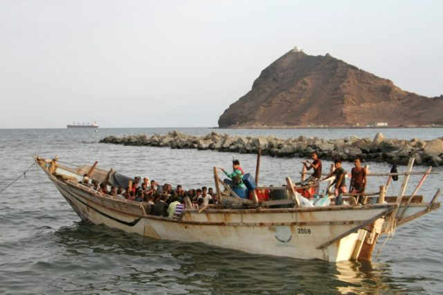 A file picture shows African illegal immigrants sitting on a boat in the southern port city of Aden on September 26, 2016, before they were deported to Somalia