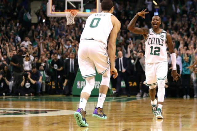 Terry Rozier of the Boston Celtics celebrates with Jayson Tatum after hitting a three point shot against the Philadelphia 76ers in Boston, Massachusetts