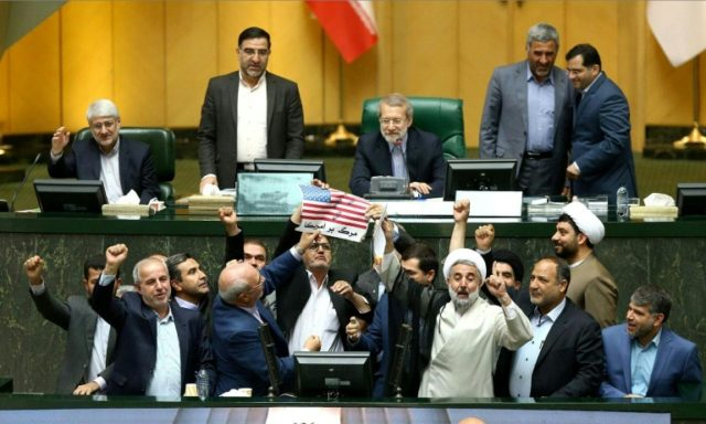 A handout picture from the Iranian Parliament shows MPs preparing to burn a US flag in the parliament's chamber in Tehran on May 9, 2018