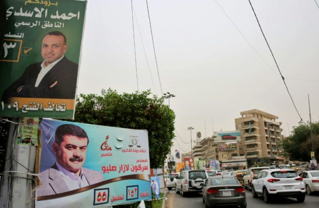 "Ahead of Iraq's upcoming parliamentary elections, an Al-Fath Alliance poster (top) reads: ""Ahmad al-Assadi, the Spokesman"". Pictured in Baghdad on May 8, 2018"
