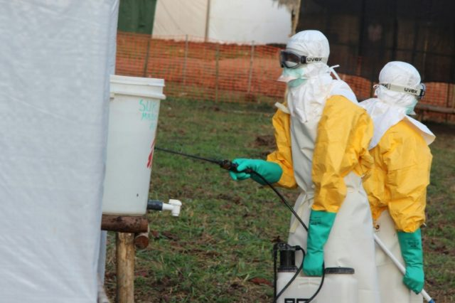 Hygienists wearing protective suits disinfect the toilets of an Ebola treatment centre in DR Congo during an earlier outbreak
