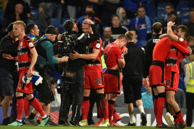 Huddersfield Town coach David Wagner (CL) celebrates with his players after a 1-1 draw with Chelsea secured top flight football next season