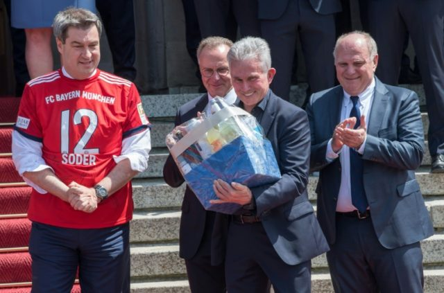 Bayern Munich's German head coach Jupp Heynckes (C) holds a present for his 73rd birthday, during a reception hosted by Bavarian State Premier Markus Soeder (L) in Munich