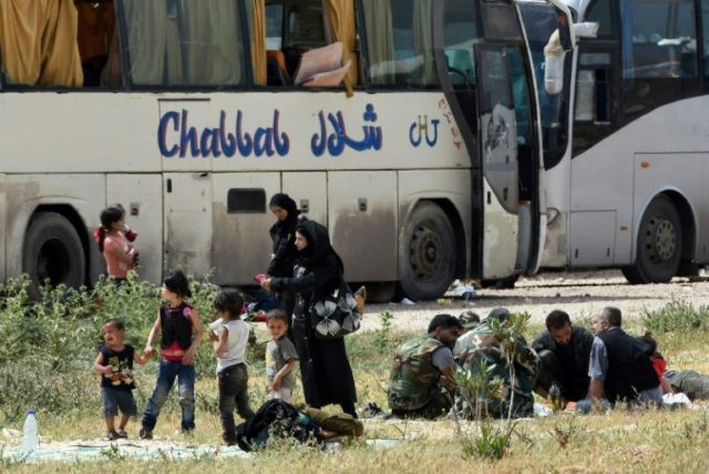 Opposition fighters and their family members evacuated from the towns of Yalda, Babila, and Beit Saham, south of Syria's capital, under a negotiated withdrawal to secure the last opposition holdouts of Damascus in May 2018