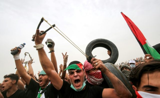 Palestinian protesters use slings to hurl stones towards Israeli forces during clashes along the border with the Gaza Strip east of Khan Yunis on May 4, 2018
